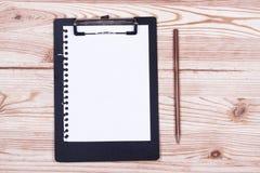 有铅笔的剪贴板在木头 免版税库存图片