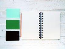 有铅笔的在白色木背景的螺纹笔记本和卡片 免版税图库摄影