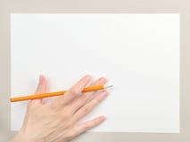 有铅笔的手在白纸板料 库存照片