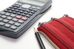 有铅笔的科学计算器和事务的红色袋子 免版税图库摄影