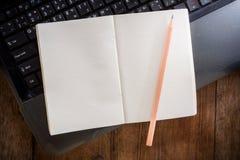 有铅笔的空白的笔记本在膝上型计算机 免版税库存图片