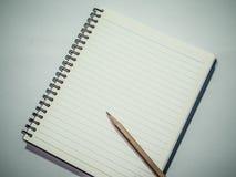 有铅笔的笔记本在灰色桌上 免版税库存图片