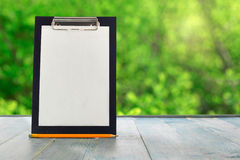 有铅笔的黑剪贴板在一张蓝色木桌上 免版税库存图片