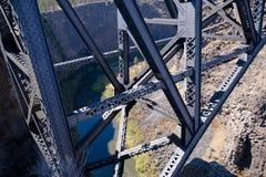 有铆钉的桁架桥高在深峡谷上 库存照片