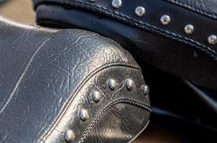 有铆钉的黑皮革摩托车马鞍 免版税库存图片