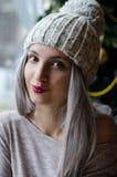 有银灰色头发的美丽的女孩在pom有葡萄酒红嘴唇的pom帽子在冬天 库存照片