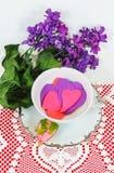 有银色修剪的俏丽的茶或咖啡杯用桃红色填装了,并且紫色纸心脏坐与桃红色的一块白色心脏小垫布上升了 库存图片