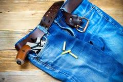 有银色左轮手枪的老蓝色牛仔裤在他的口袋 库存照片