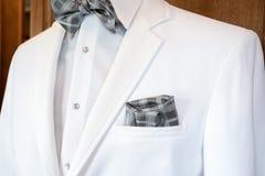 有银色格子花呢披肩蝶形领结的白色无尾礼服 免版税库存图片