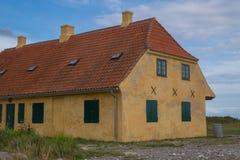有铺磁砖的屋顶的老黄色房子 免版税库存图片