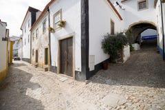有铺路石的狭窄的舒适街道在Obidos一个小葡萄牙镇  库存图片