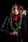 有链子和一朵红色玫瑰的美丽的少妇 免版税库存照片