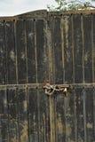 有链子和挂锁背景的被风化的金属门 免版税库存照片