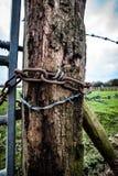有链子和铁丝网的老门岗位 免版税库存照片