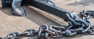 有链子的重的铁金属船船锚在灰色沥青 免版税图库摄影