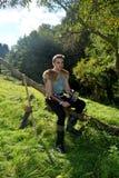 有链衬衣的年轻中世纪射手坐在自然在阳光下,在手、箭头和曲线st的角制酒杯的分支 免版税库存照片