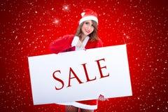 有销售广告牌的圣诞老人妇女 库存照片
