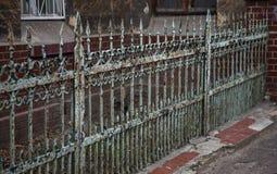 有锋利的矛和破裂的油漆的老伪造的铁生铁篱芭时常 打破的白色肮脏的被放弃的篱芭 库存图片