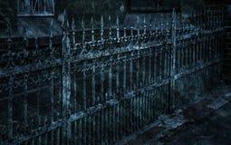 有锋利的矛和破裂的油漆的老伪造的铁生铁篱芭时常 打破的白色肮脏的被放弃的篱芭 免版税图库摄影