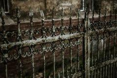 有锋利的矛和破裂的油漆的老伪造的铁生铁篱芭时常 打破的白色肮脏的被放弃的篱芭 库存照片