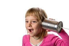 有锡罐电话的-表示女孩惊奇 免版税库存照片