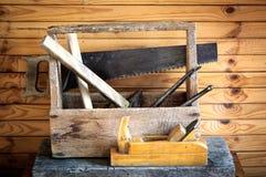 有锤子、锯、飞机和钳子的老葡萄酒工具箱在木匠业方面 库存照片