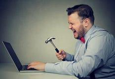 有锤子和残破的膝上型计算机的恼怒的人 免版税库存图片