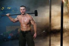 有锤子的坚强的肌肉人在肩膀 图库摄影