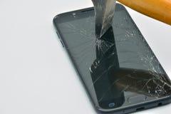 有锤子的残破的流动手机屏幕 免版税图库摄影