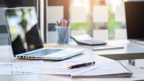 有键盘、报告图表图、笔和桌的企业书桌 库存图片