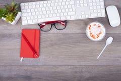 有键盘、老鼠、笔记、笔、玻璃和desse的企业书桌 库存照片