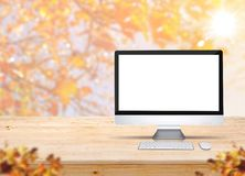 有键盘和老鼠的计算机桌面在与迷离的木桌上 免版税库存照片