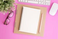 有键盘和铅笔的空白的笔记本在桃红色背景,笔记本平的被放置的照片您的消息的 免版税库存图片