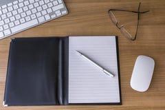 有键盘的书桌和笔记薄和玻璃 免版税库存图片