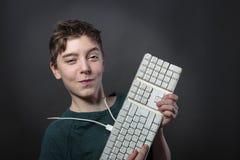有键盘的微笑的十几岁的男孩 免版税图库摄影