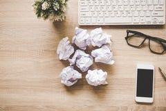 有键盘老鼠和被弄皱的纸球的企业与图表的工作场所,纸和图 库存照片
