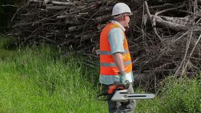 有锯的伐木工人谈话在smarth电话在堆分支附近 影视素材