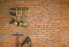 有锹和杓子垂悬的砖墙 库存图片