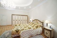 有镀金面双人床和床头柜的豪华卧室 库存照片