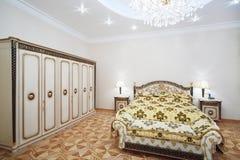 有镀金面双人床和衣橱的豪华卧室 免版税库存图片