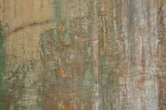 有镇压、深绿色油漆和土抓痕和污点的老被打击的灰色黄色混凝土墙  E 免版税库存图片