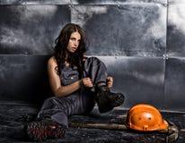 有镐和盔甲的美丽的性感的工作者 诱人和美丽的妇女矿工坐在钢的一个地板 库存照片