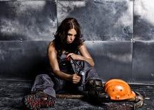 有镐和盔甲的美丽的性感的工作者 诱人和美丽的妇女矿工坐在钢的一个地板 免版税库存图片