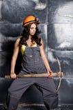 有镐的美丽的性感的工作者 钢背景的诱人和美丽的妇女矿工 免版税库存照片
