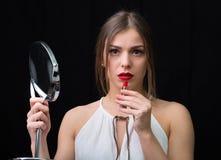 有镜子和一支红色唇膏的妇女 免版税图库摄影