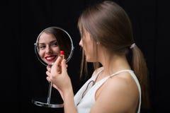 有镜子和一支红色唇膏的妇女 库存图片