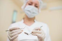 有镜子和牙周探险家的年轻女性牙医诊所的,特写镜头,在牙齿仪器的焦点 免版税图库摄影