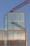 有镜子玻璃摩天大楼的起重机建设中 免版税库存图片