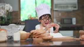 有镜片、激发用第一次经验的鸡蛋的厨师帽子和围裙的逗人喜爱的矮小的亚裔男孩对家庭k的烘烤的面包店 股票视频