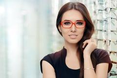 有镜片的少妇在光学商店 免版税库存图片